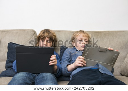 Boys playing online games on digital tablets while relaxing on sofa at home - stock photo