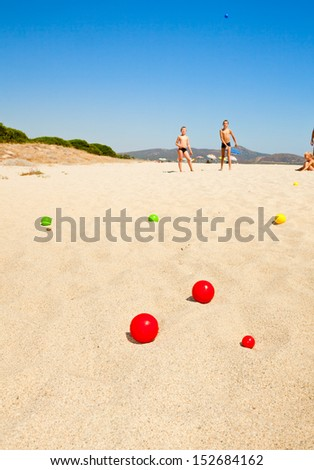Boys playing petanque on a beach, focus on balls - stock photo