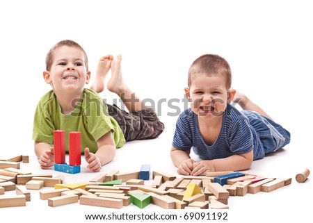 Boys playing whit blocks isolated on white and showing mouth and teeth - stock photo