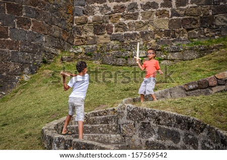 Boys playing with wooden swords - stock photo