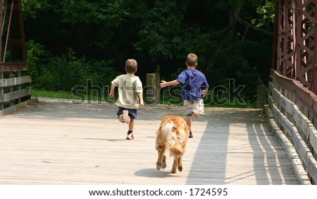 Boys running with Dog Chasing - stock photo