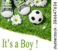 Boys shoes and a football ball on on the grass. Concept for baby shower - stock photo