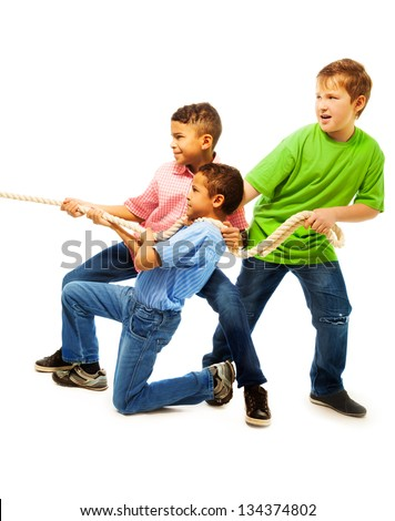 Boys team of three 8-11 years old kids pulling the rope standing isolated on white