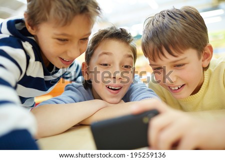Boys using a new smartphone - stock photo