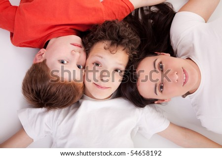 boys with woman, lying on the floor with heads together. Studio shot.