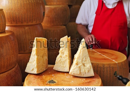 BRA - SEPTEMBER 22: Cut pieces and wheels of Parmesan - italian cheese made from raw cow's milk, often grated over dishes and named after producing areas near Parma, Italy on September 22, 2013. - stock photo