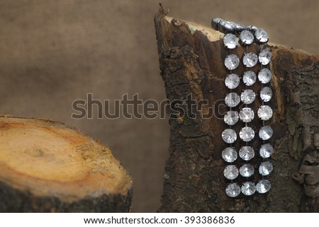Bracelet hanging on the log - stock photo