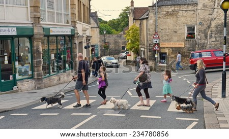 BRADFORD ON AVON - AUG 17: People use a zebra crossing in the town centre on Aug 17, 2014 in Bradford on Avon, UK. Zebra crossings originated in the UK in 1949 and have since been adopted worldwide. - stock photo