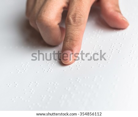 Braille book with visual impaired/ low vision person's hand/ finger touching paper texture reading the sign: Accessibility in equal education concept: Human rights to learn: National literacy month - stock photo