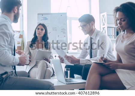 Brainstorm. Young beautiful woman discussing something with her coworkers while sitting on the couch at office  - stock photo