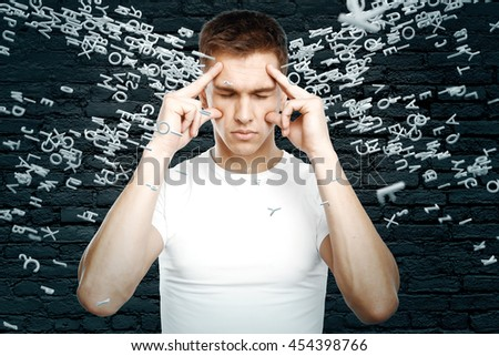 Brainstorming concept with thinking young guy surrounded with abstract letters on black brick wall background - stock photo