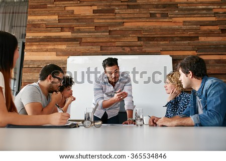 Brainstorming in a boardroom of creative office . Young creative people sitting at the table and discussing new projects. - stock photo