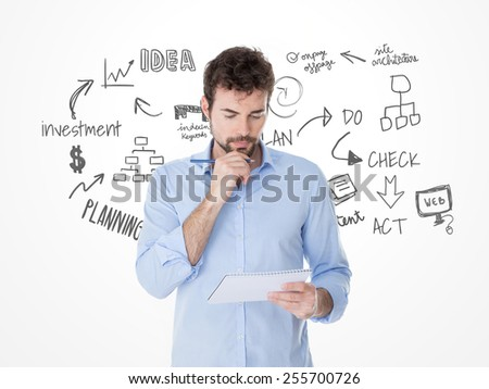 brainstorming of young man with one hand on his chin - stock photo