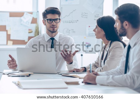 Brainstorming with business partners. Young handsome man in glasses gesturing and discussing something with his coworkers while sitting at the office table - stock photo