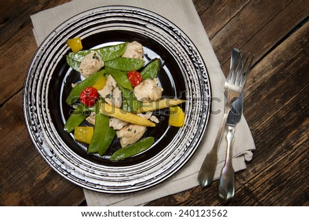 Braised chicken breast with young peas, corn, bell pepper, thyme and cherry tomatoes - stock photo