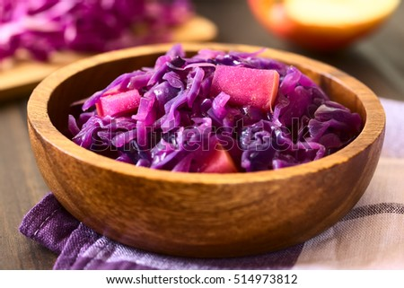 Braised red cabbage with apple in wooden bowl, with ingredients in the back, photographed with natural light (Selective Focus, Focus in the middle of the dish)