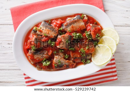 Braised sardines in tomato sauce with lime and parsley close-up on a plate. Horizontal view from above
