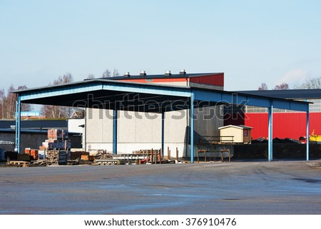 BRAKNE-HOBY, SWEDEN - FEBRUARY 07, 2016: An outdoor storage area under a steel roof in an industrial area. Industrial building in background. Logos visible.