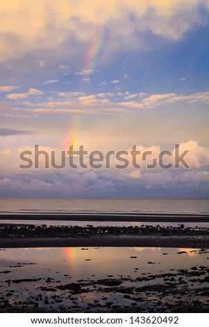 Bramble Bay, Brisbane, at sunset, with reflection of the rainbow in the still water below - stock photo