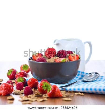 Bran flakes with fresh raspberries and strawberries on blue checkered cloth and a pitcher of milk over white background. Healthy eating choice concept - stock photo