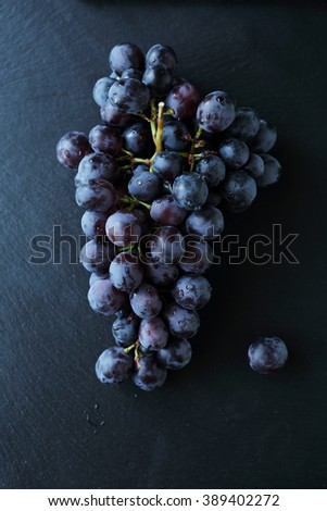 branch of blue grapes on slate, food top