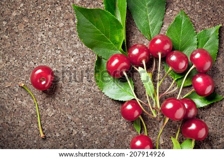 Branch of cherry berries on wooden background, closeup shot - stock photo