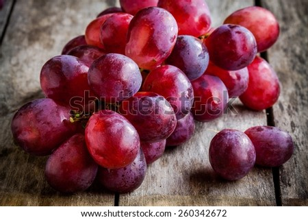 branch of ripe organic grapes on wooden rustic background - stock photo