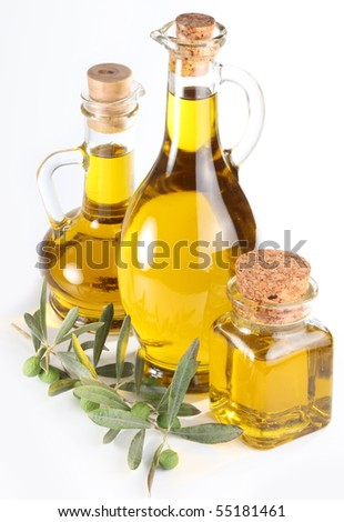 Branch with olives and a bottles of olive oil isolated on white - stock photo