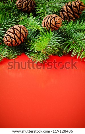 Branches of Christmas tree with pine cones on festive red background - stock photo