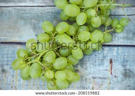 branches of fresh green grape on a wooden surface