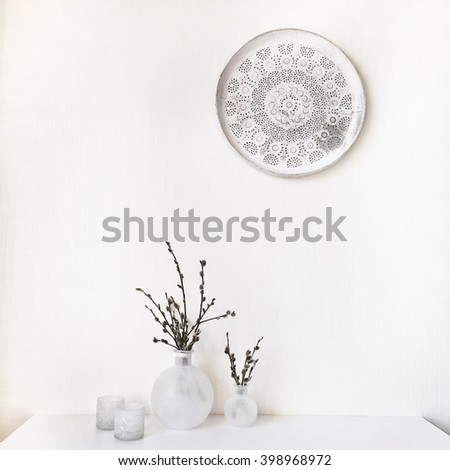 Branches of pussy-willow in white vase at white table and white vintage tray - stock photo