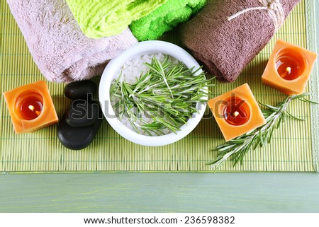 Branches of rosemary and sea salt in bowl, towels, candles and bottle with massage oil on wooden background. Rosemary spa concept - stock photo
