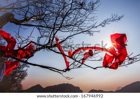 branches on top of the mountains are tied with red clothes as the Chinese believe that it will bring luck and happiness.  - stock photo