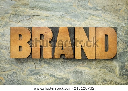brand - a word in vintage letterpress wood type on a green slate rock background - stock photo