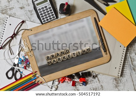 Brand Marketing concept on blackboard with note pad, pencils and calculator