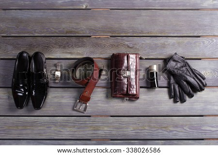 Brand men's accessories and shoes on a wooden background. - stock photo