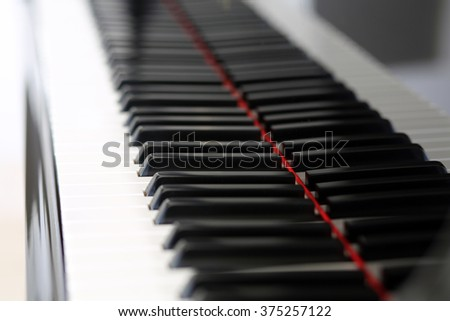 Brand new baby grand keyboard with a single key in focus - stock photo