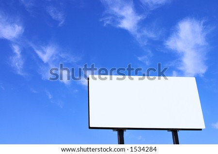 Brand new billboard and a brilliant blue sky with wispy clouds. - stock photo