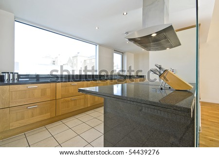 Brand new contemporary open plan kitchen with modern appliances and cons - stock photo