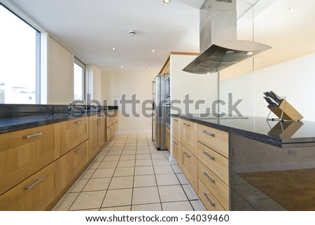 Brand new contemporary open plan kitchen with modern appliances and double amirican style fridge - stock photo
