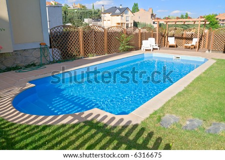 Brand new garden swimming pool with sparkling fresh water. Relaxing pergola with wooden garden furniture. - stock photo