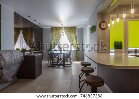 Brand new modern kitchen. Open space kitchen and white counter top, brown cupboard, leather stool, hardwood floor, black stove, stainless fridge. Kitchen interior design. Luxury kitchen furniture.