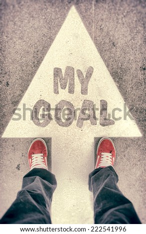 Brand new red shoes from above standing on my goal sign - stock photo