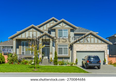 Brand new residential house with car parked on driveway in front. Big family house with double garage door and blue sky background. British Columbia, Canada. - stock photo
