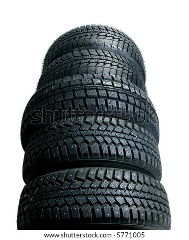 Brand new tires stacked up and isolated on white background - worms view - stock photo