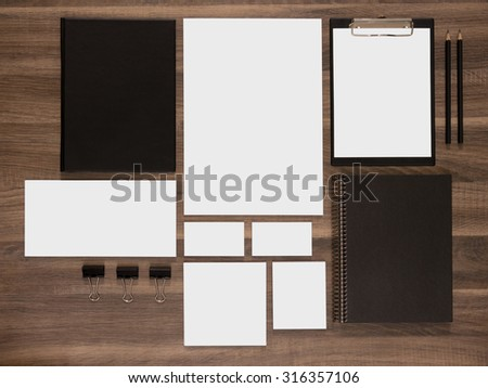 Branding mockup collection on brown wooden desk. Blank business cards with documents, envelopes and black notepads. - stock photo