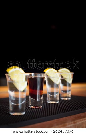 Brandy and  three tequila shots with lemon on a bar ribber mat. Shallow DOF and toned - stock photo