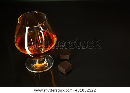 Brandy glass and chocolate on black background. Brandy whiskey glass. Cognac france.