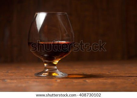 Brandy glass on the wooden table - stock photo