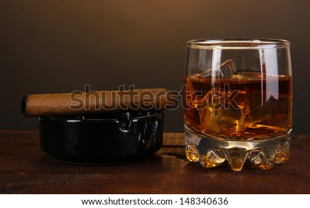 Brandy glass with ice and cigar on wooden table on brown background - stock photo